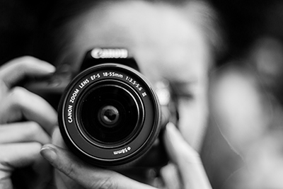 Closeup of woman holding a camera in black and white