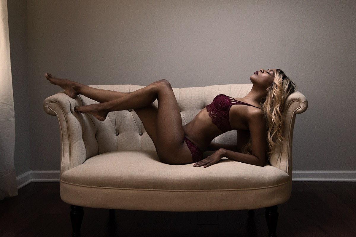 Moody boudoir image of woman on settee