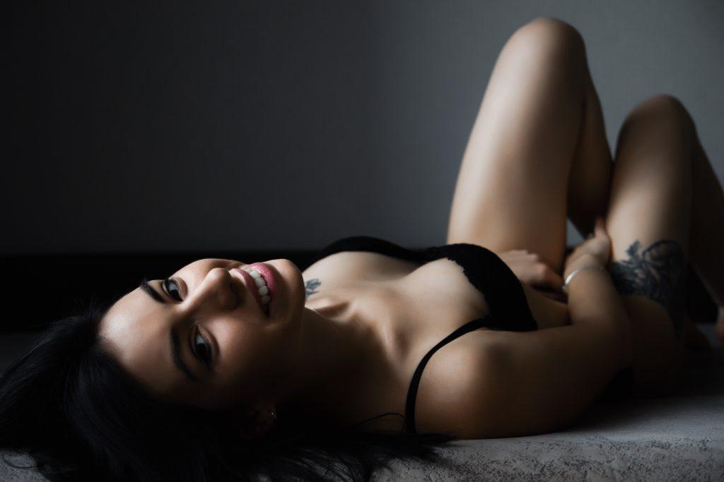 Woman in black bra in dark moody boudoir photo