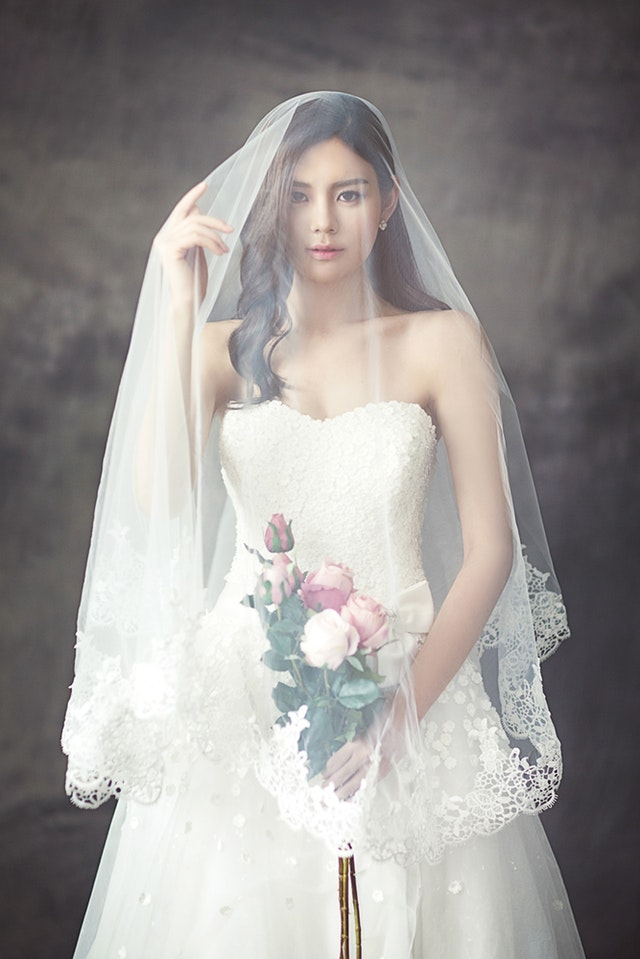 Bride in gown and veil holding bouquet
