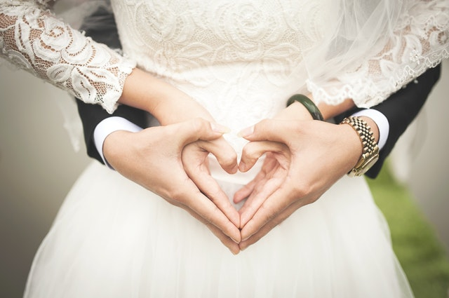 Bride and groom forming heart shape with hands