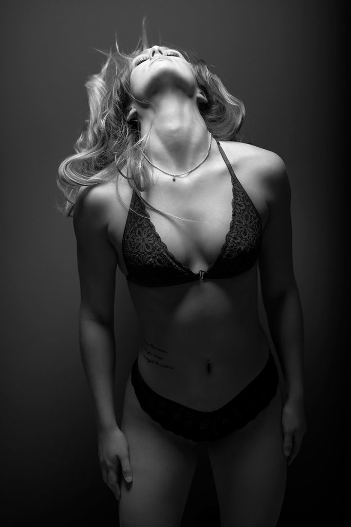 Black and white boudoir photo of young blonde woman with head back.