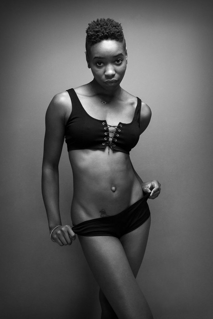 Black and white boudoir photo of black woman in black bra and bottoms