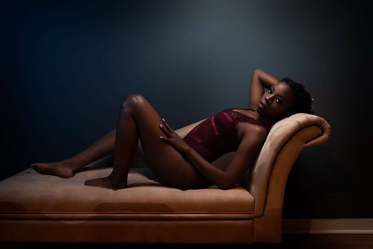 Dramatic moody boudoir image of young black girl in maroon teddie reclined on beige lounger