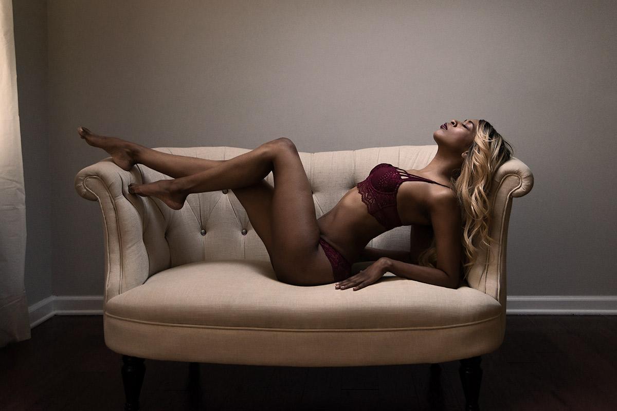 Moody boudoir image of woman on settee