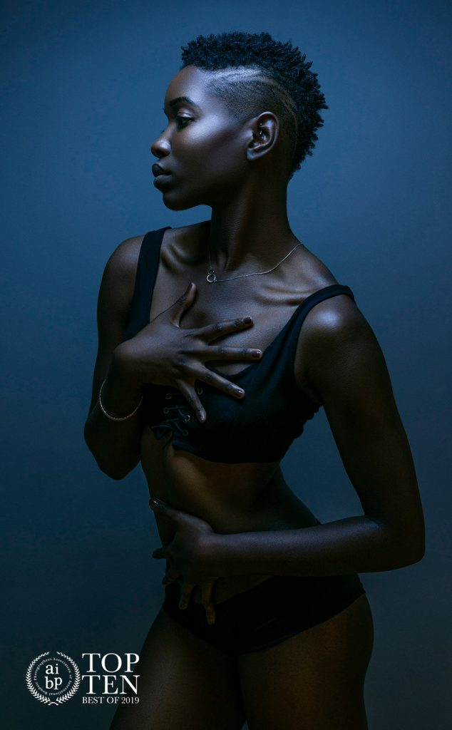 Moody boudoir image of young black woman in blue light