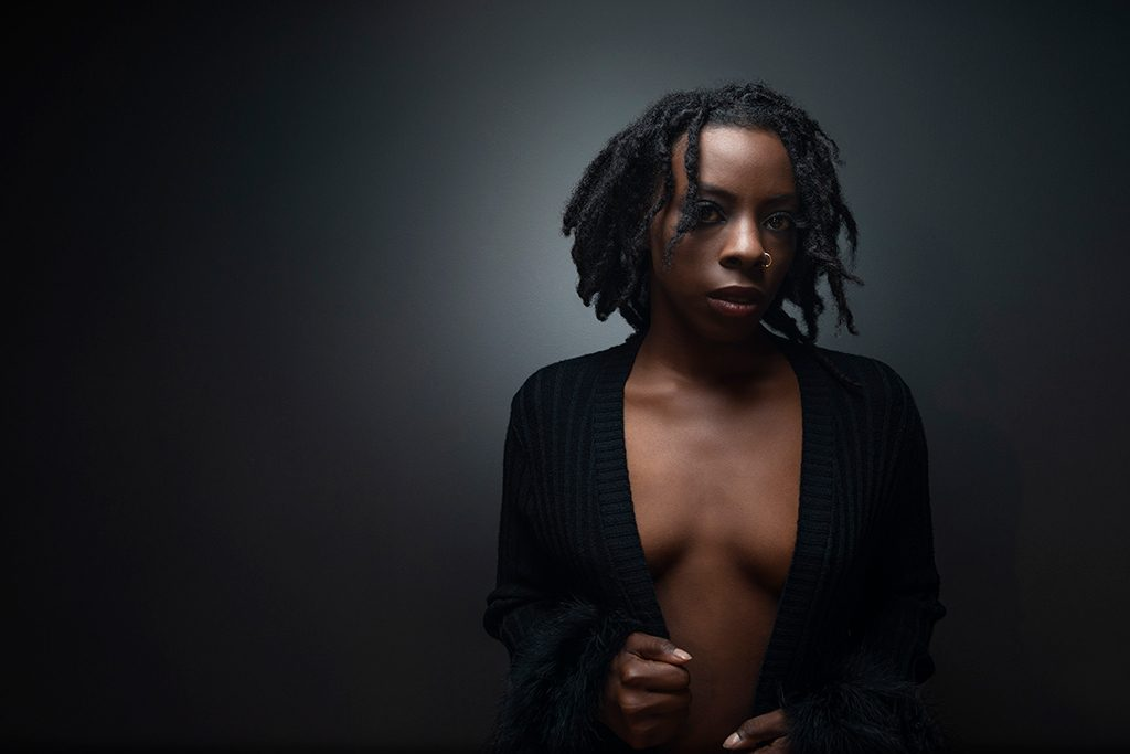 Dark and moody boudoir portrait of young black woman