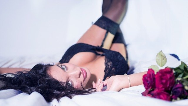 Boudoir images of woman in black bra and panties with black fish net stockings