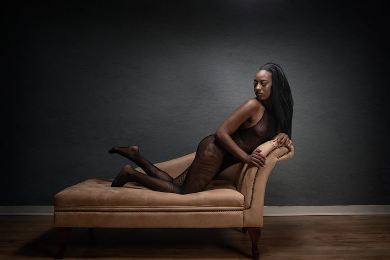 Boudoir image of woman in fishnet body stocking
